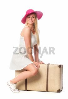 mädchen sitzt auf einem reisekoffer und wartet