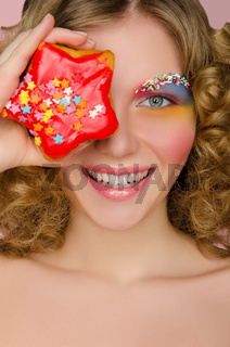 Young woman with donut in face