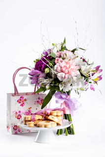 Pastel bouquet from pink and purple gillyflowers on white with gift and cookies