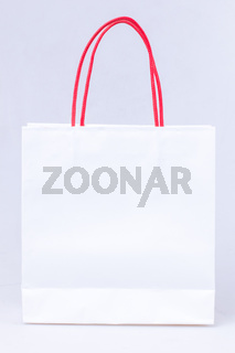 white paper bag with red handle