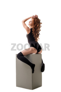Sexy red-haired girl posing while sitting on cube