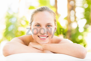 Close up portrait of a beautiful young woman on massage table