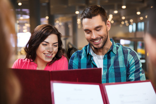 smiling couple with friends and menu at restaurant