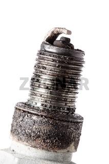 Auto service. Old spark plug as spare part of car.