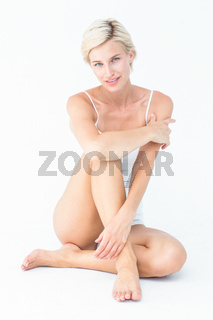 Gorgeous blonde sitting on the floor smiling at camera