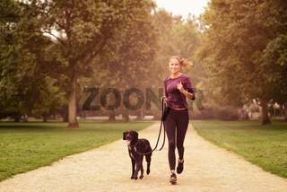 Gesunde Frau joggt mit ihrem Hund