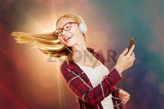 Tanzende junge Frau hört Musik über Kopfhörer
