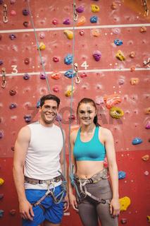 Couple climbing up rock wall