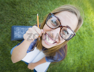 Wide Angle of Pretty Young Woman with Books and Pencil