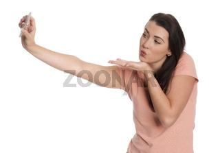 junge frau zeigt einen pustekuss und macht ein selfie