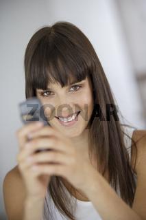 Junge laechelnde Frau mit Mobiltelefon