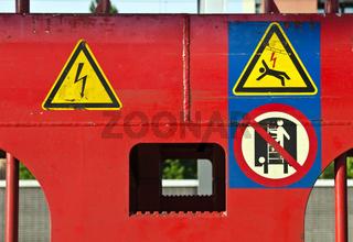 Unterschiedliche Warnschilder an einem rot lackierten Eisenbahnwagen