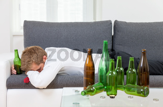 Depressed businessman drunk at home with empty bottles on table