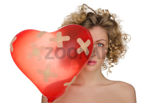 Balloon in shape of heart and hurt woman
