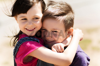 two happy kids hugging outdoors