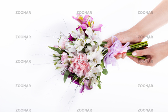 Hands holding a pink bouquet from gillyflowers and alstroemeria on white