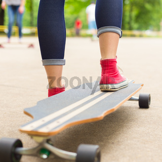 Girl practicing urban long board riding.