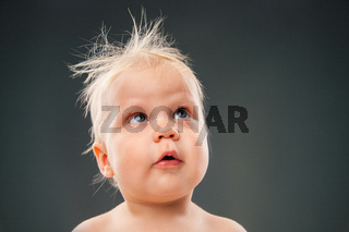 Headshot of adorable baby with messy hair