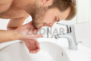 Man washing his face in the bathroom sink