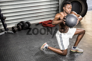 Muscular man training with medicine ball