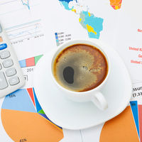 Coffee cup and calculator over financial documents - studio shot