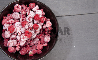 Frozen raspberries on dark wooden background