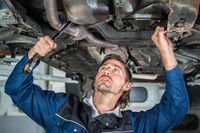 Mechanic repairing a lifted car wit