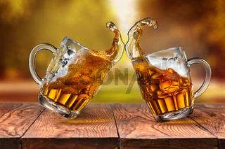 Beer in glasses with splash on wooden table against autumn leaves