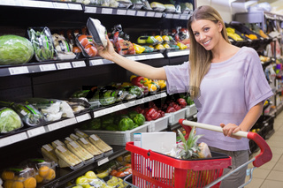 Smiling woman taking a vegetables in the aisle