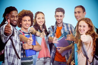 Composite image of smiling group of students doing thumbs up