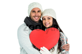 Smiling couple holding paper heart