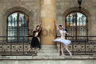 Two beautiful ballerinas dancing together around a column