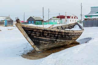 Wooden fishing boat on the winter snow-covered coast.