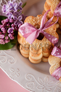 Butter cookies with pink ribbon and lilac flowers, top view