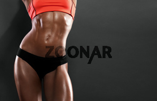 The body of a young athletic girl on dark background