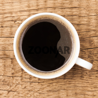 Black coffee in white ceramic cup on wooden table