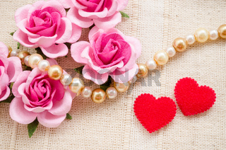 Red heart and pink rose on fabric background.