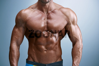 Attractive male body builder on blue background