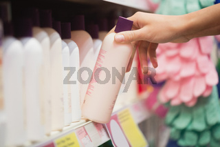 Focus on hands picking shampoo