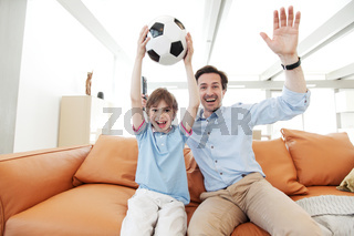 father and son wathcing football