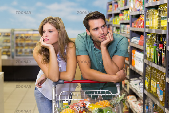 Serious brght couple buying food products