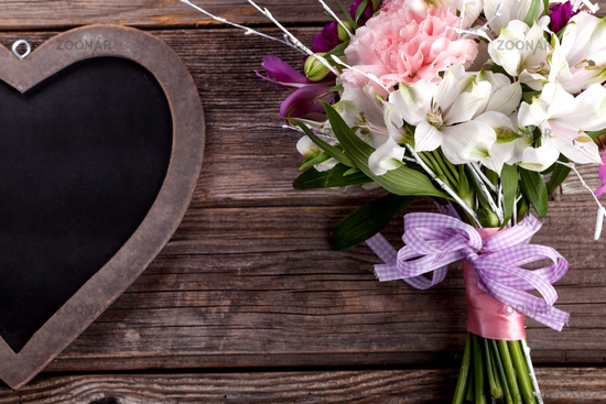 Rustic bouquet from gillyflowers and alstroemeria on old wooden background with wooden heart