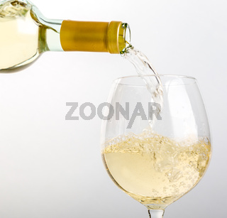 White wine pouring in glass from a bottle