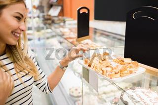 Side view of woman choosing dessert