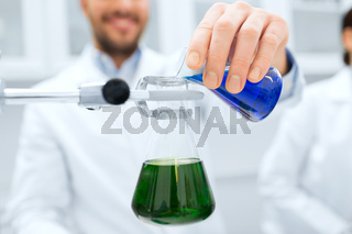 close up of scientist filling test tubes in lab