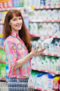 Portrait of woman with shopping basket holding detergent