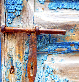 rusty metal     nail dirty stripped paint in the blue wood door and morocco knocker