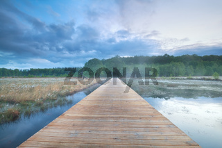 wooden road through swamp with cotton-grass