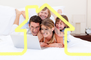 Composite image of loving family looking at a laptop lying down on bed