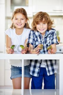 Zwei fröhliche Kinder halten Kiwi Hälften